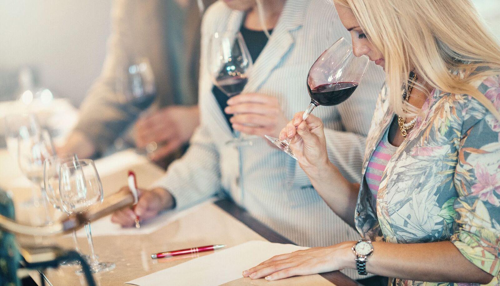 En dame som smaker på vin på vinsmaking. Ting å gjøre i Bergen.