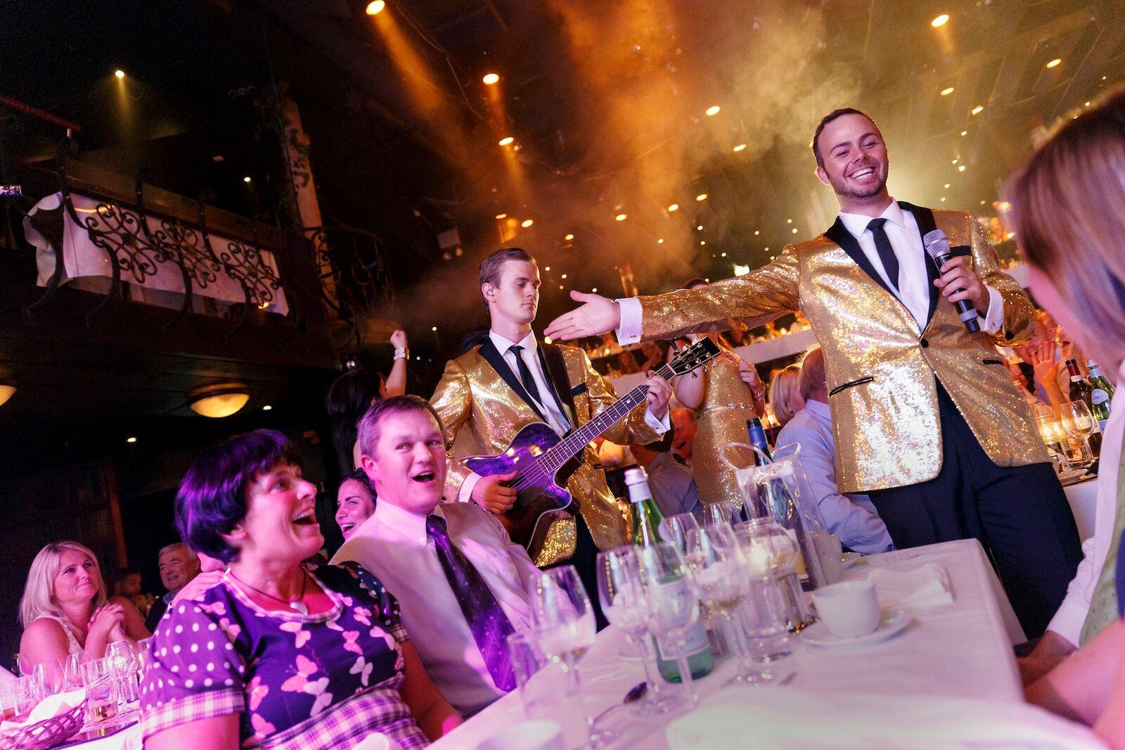 Mennesker rundt middagsbord som underholdes på wallmans salonger i oslo. En hyggelig kveld som passer som 50 års gave til mann som elsker musikk, dans og god mat.