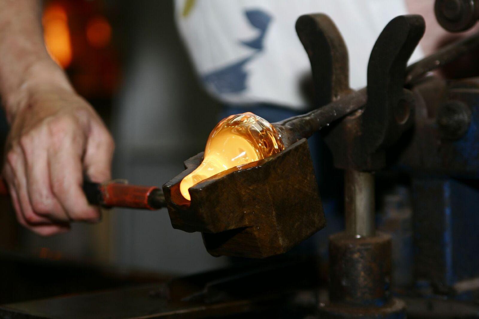 glassmester jobber med glødende glass