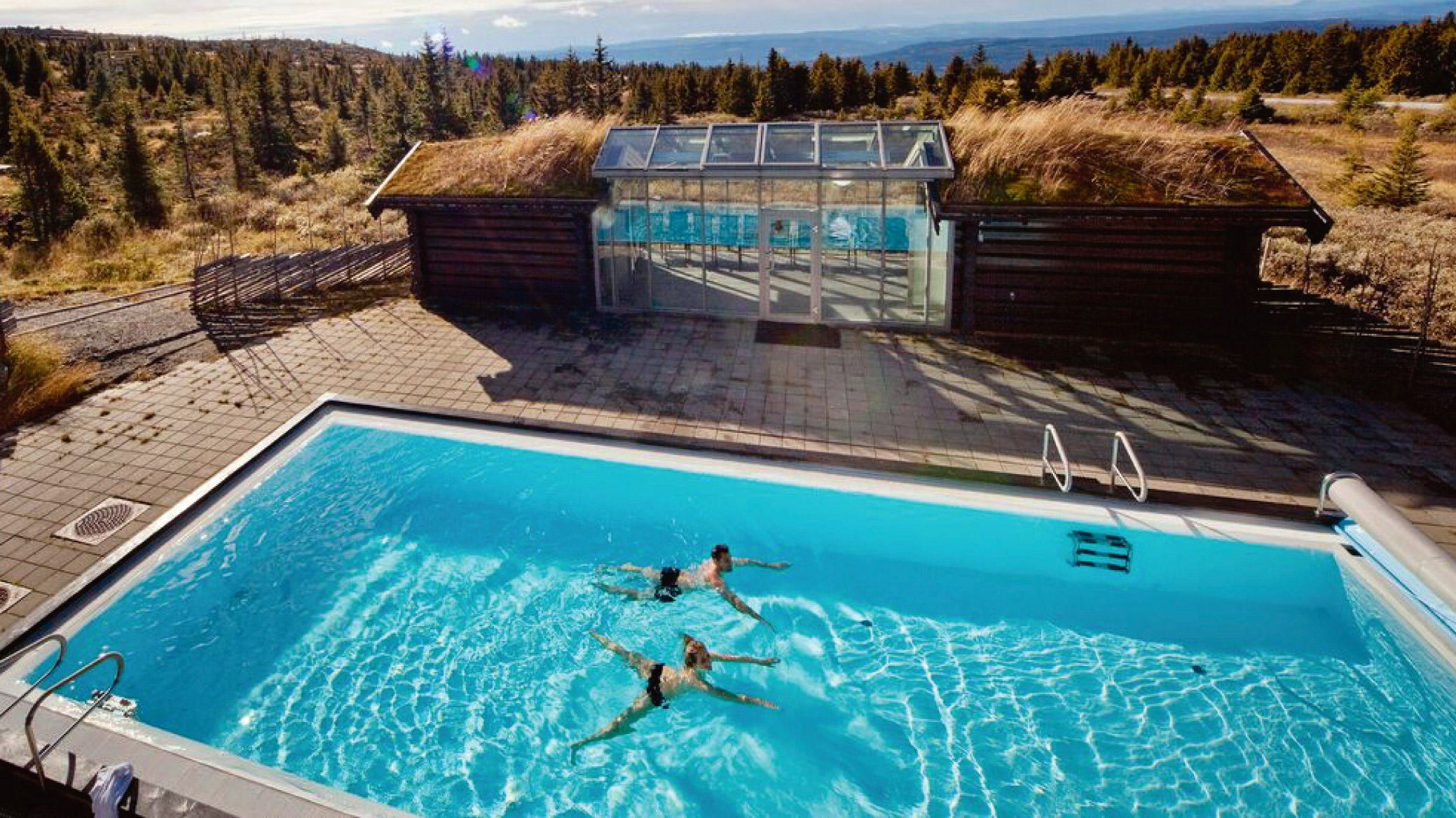 Par som svømmer i et utendørs basseng på fjellet. En super gave til brudeparet 2017.