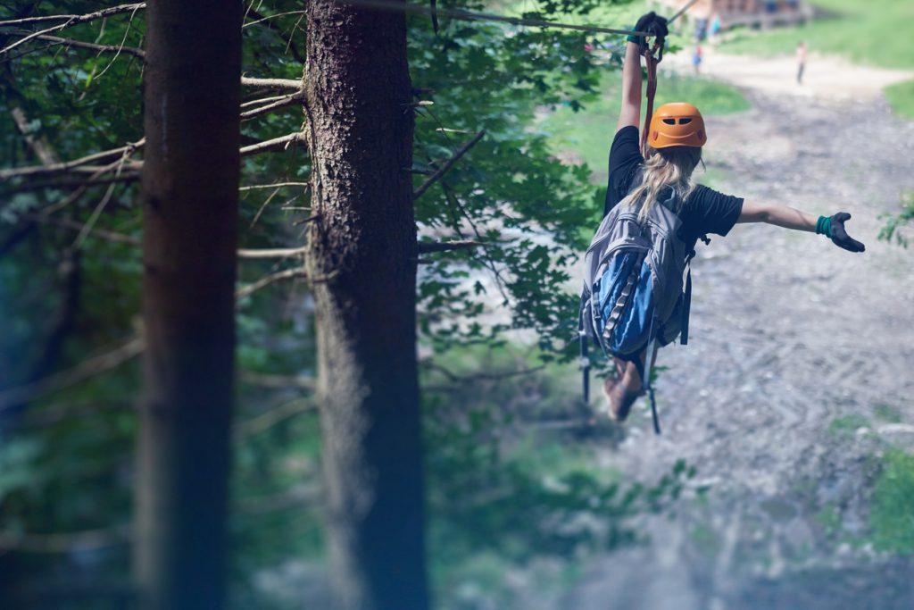 En jente som kjører zipline i skogen. Her finner du våre beste forslag til 30 års gaver.