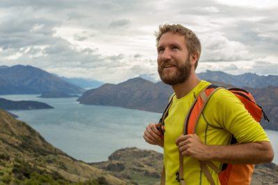 Ung mann på gåtur som står på toppen av et høyt fjell med fantastisk utsikt til fjell og fjord. Det ser ut som han nyter utsikten og har det veldig bra. En perfekt bursdagsgave til han under 700 kroner finner du her.