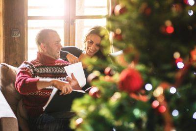 Par som leser en bok i stuen på juleaften. Her finner du gode gavetips til perfekt julegave til kjæresten