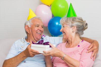Et eldre ektepar som gir hverandre gaver med partyhatter på hodet, smilende og glade. finn en gave til 60 åring du er glad i finner du her!