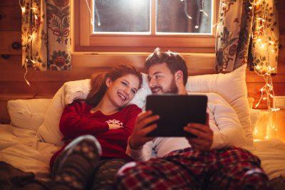 Et par som ligger på sofaen og ser på ipad. Kjøp årets julegaver på nett.