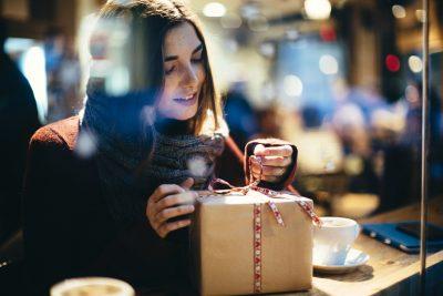 En dame som åpner en julegave. Her finner du julegavetips til henne 2017.