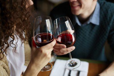 Par som skåler i rødvin og smiler. Her finner du gavetips så du kan finne en perfekt gave til kjæresten