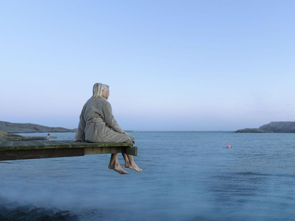 Et par som sitter på en brygge kledd i morgenkåper mens de skuer ut over et stille hav. En romantisk overnatting ved havet er et godt tips til bryllupsgave til paret som har alt.