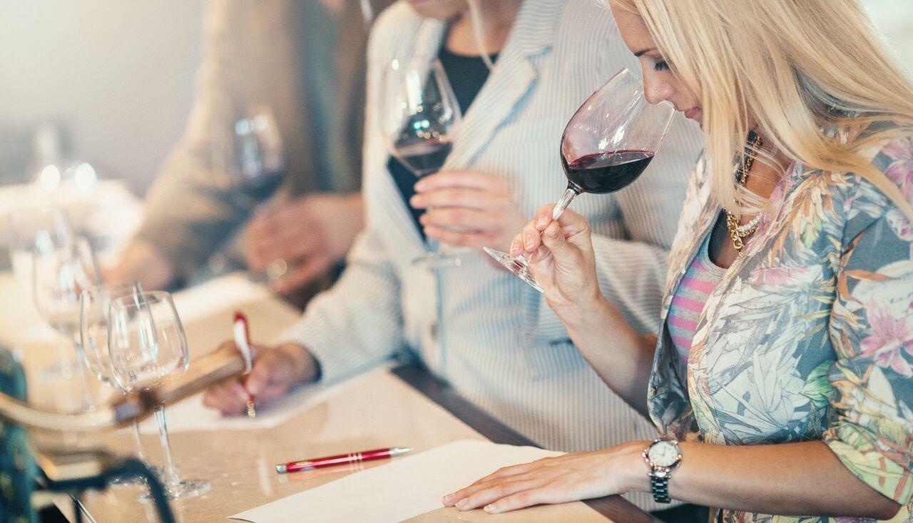 Blond dame som smaker på rødvin på vinkurs. Gi bort vinsmaking for to i valentinesgave 2018.