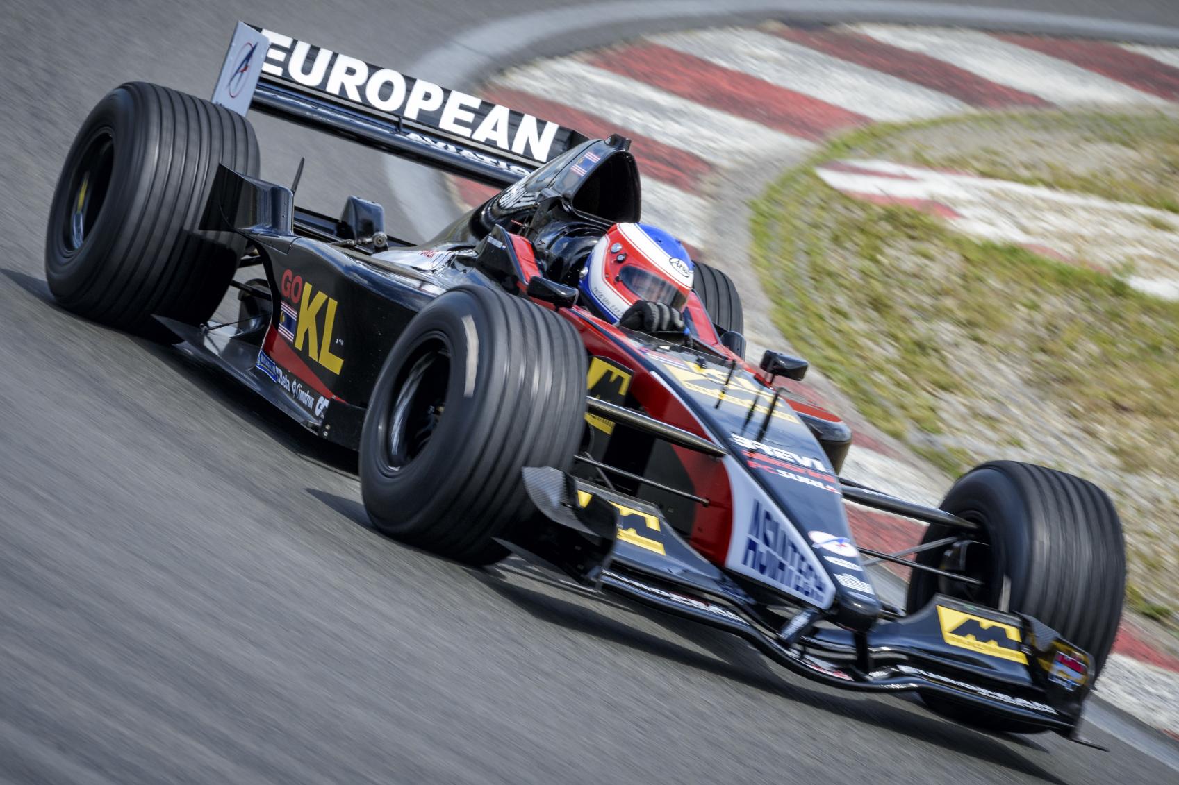 Formel1-bil kjører i full fart på bane.