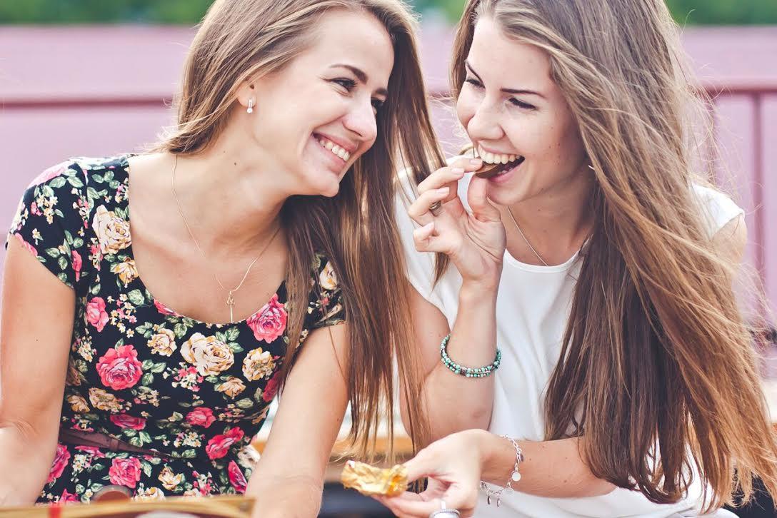 to venninner spiser sjokolade og ler. Det er sommer og de koser seg.