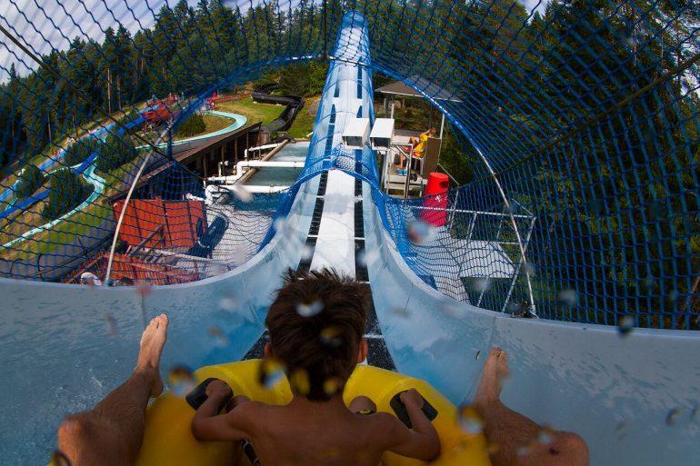 En gutt som sitter øverst i en vannsklie. En dag i sommerland i bø er en av mange opplevelser i Norge for barn hos YouWish.no.