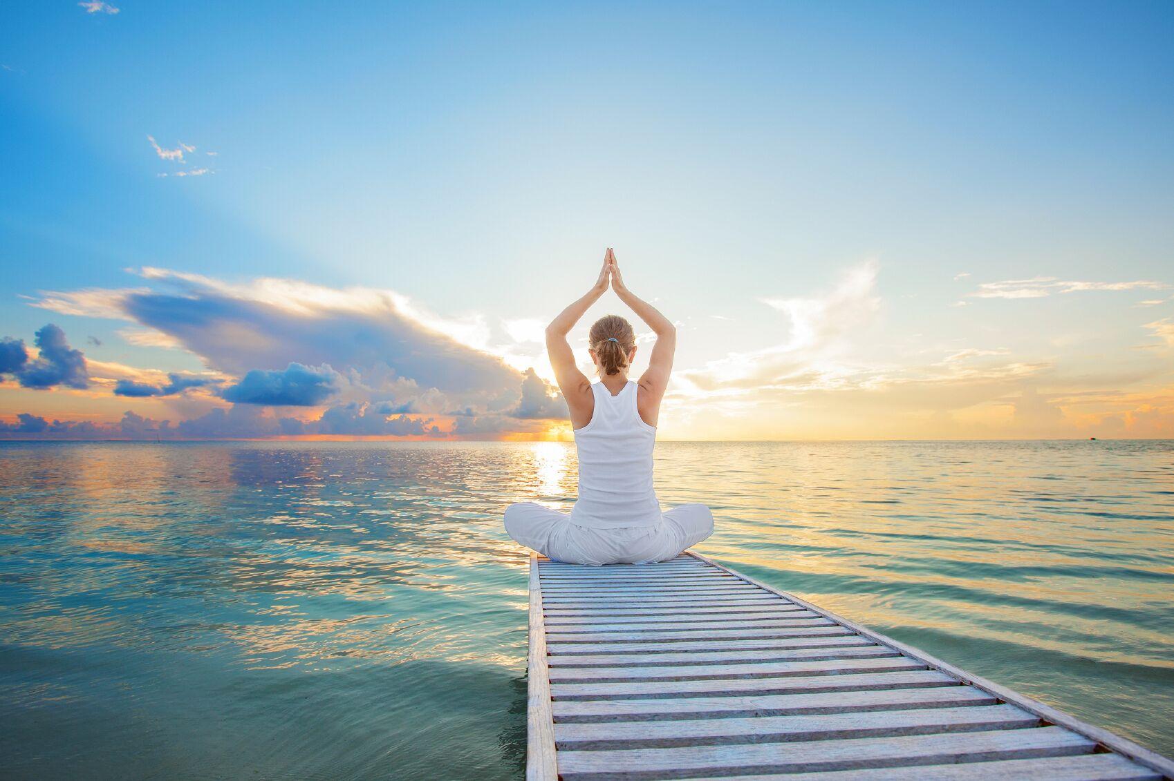En dame som sitter på bryggen og mediterer ved sjøen til en nydelig solnedgang. En perfekt 18 års gave til datter.