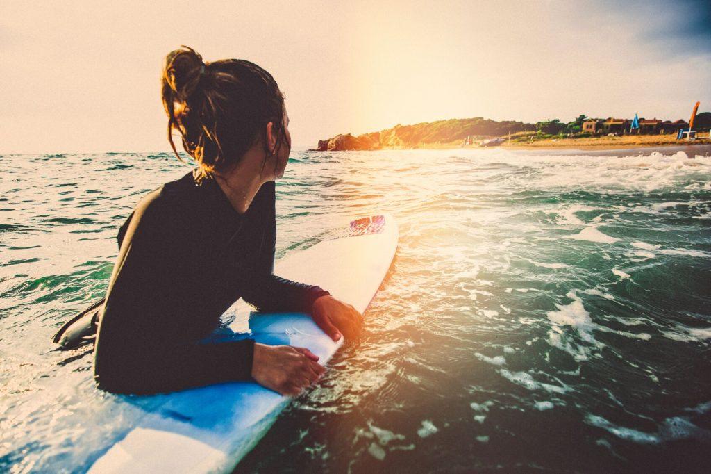 Jente på surfebrett i vannkanten. En spennende 18 års gave til datter.