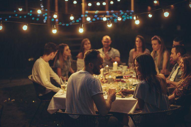 Bilde av glad vennegjeng som spiser middag rundt et stort bord. Perfekt gave til vertinne.