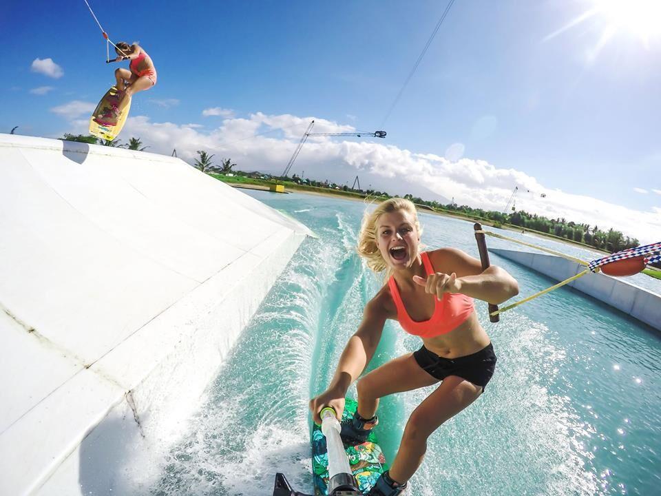 Blond ung jente som står på wakeboard i kabelpark. Kjærestetur sommer 2017.