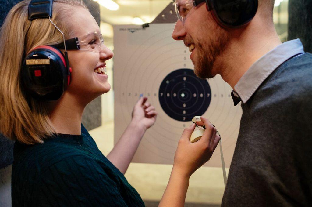 Par som har sjekker skudd på en målskive og smiler mot hverandre. Kjærestetur sommer 2017