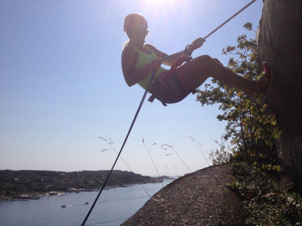 En dame som klatrer opp en fjellvegg med utsikt til fjorden. Kjærestetur sommer 2017.