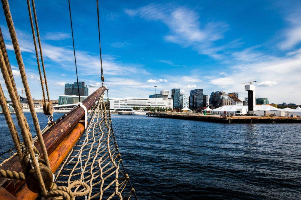 En båt på tur i Oslofjorden med utsikt til operaen og Bjørvika. Ting å gjøre i Oslo om sommeren.