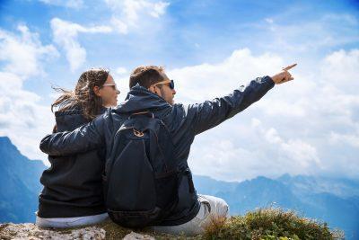 Par på toppen av fjell som holder rundt hverandre og peker mot utsikten. Kjærestetur sommer 2017.