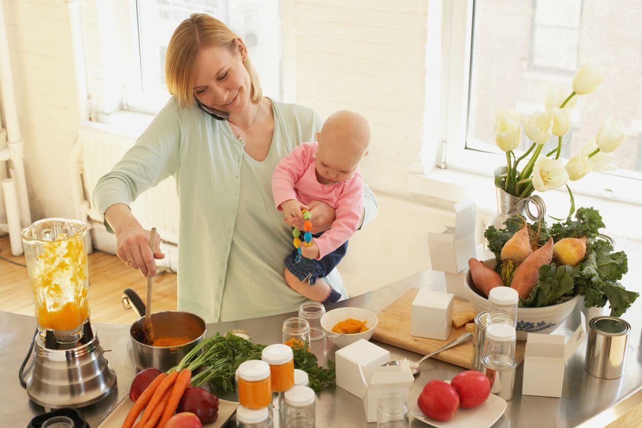 En mamma som lager mat med baby på armen. Babyshower gavetips finner du her.