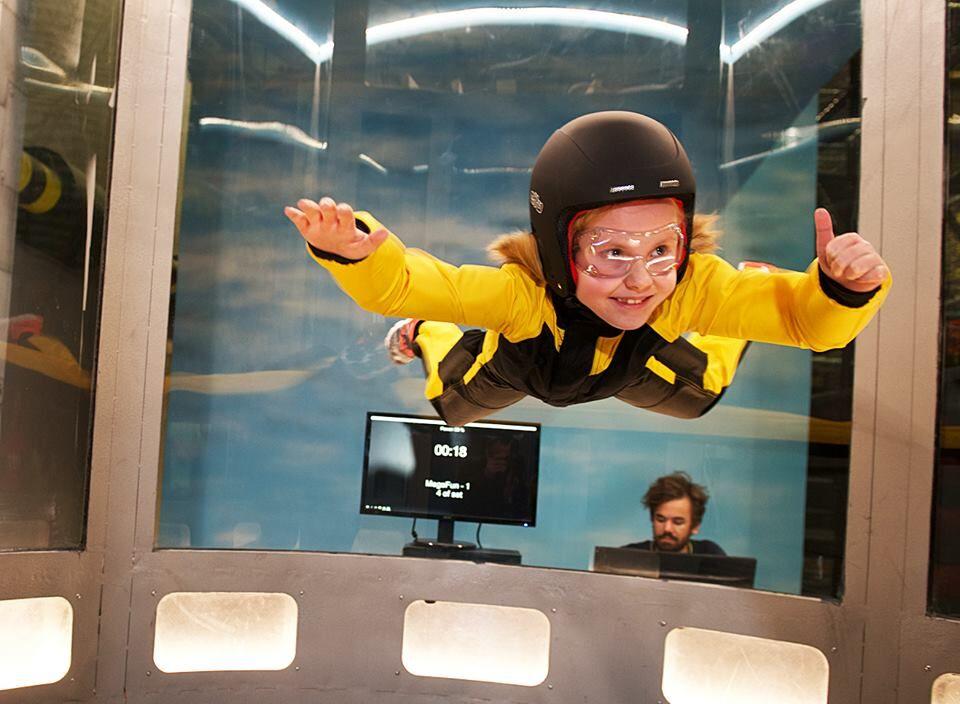 En jente i en vindtunnel som gir tommel opp. Dette er en av mange opplevelser i Norge for familien.