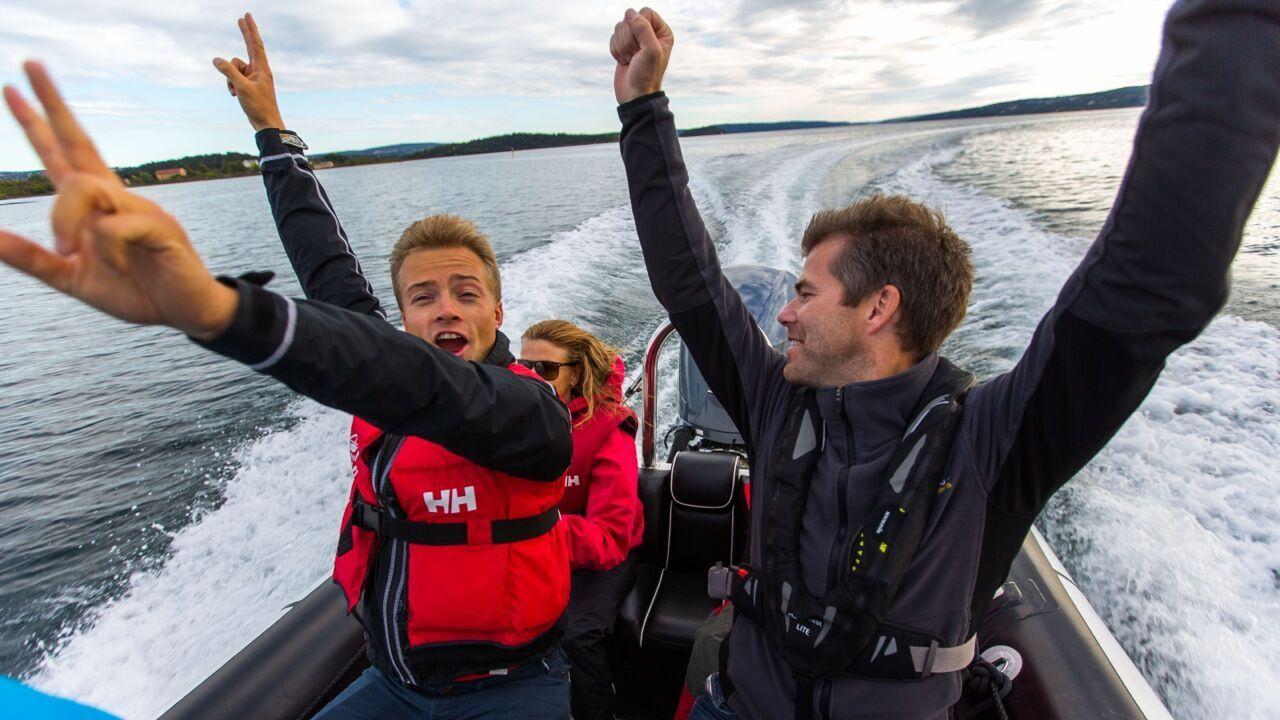 Gutter som hever armene over hodet på rib båttur. Aktiviteter i Bergen for barn finner du her.