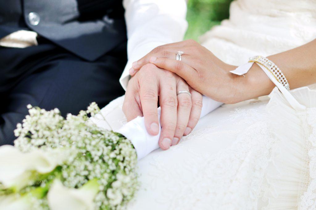 Brudepar som holder hender med giftering på hver sin finger. Etikette regler for bryllup finner du her.