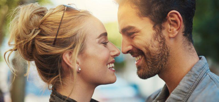 Par som smiler mot hverandre. Her deler vi ting å gjøre med kjæresten.