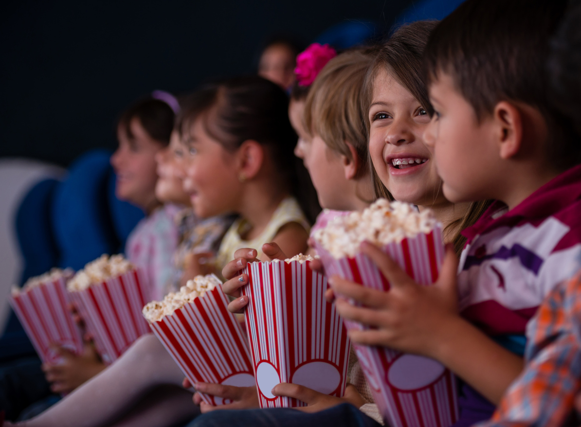 En gruppe barn på kino med popcorn. Aktiviteter i Bergen finner du her.