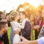 Nygift brudepar som kysser i en hage omgitt av gode venner. Etikette regler for bryllup finner du her.