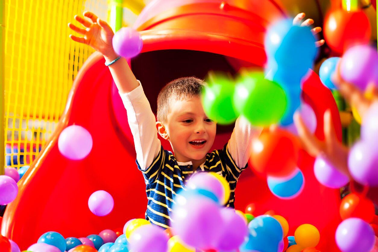 En gutt som koser seg på sklie i lekeland. Aktiviteter i Bergen for barn finner du her.