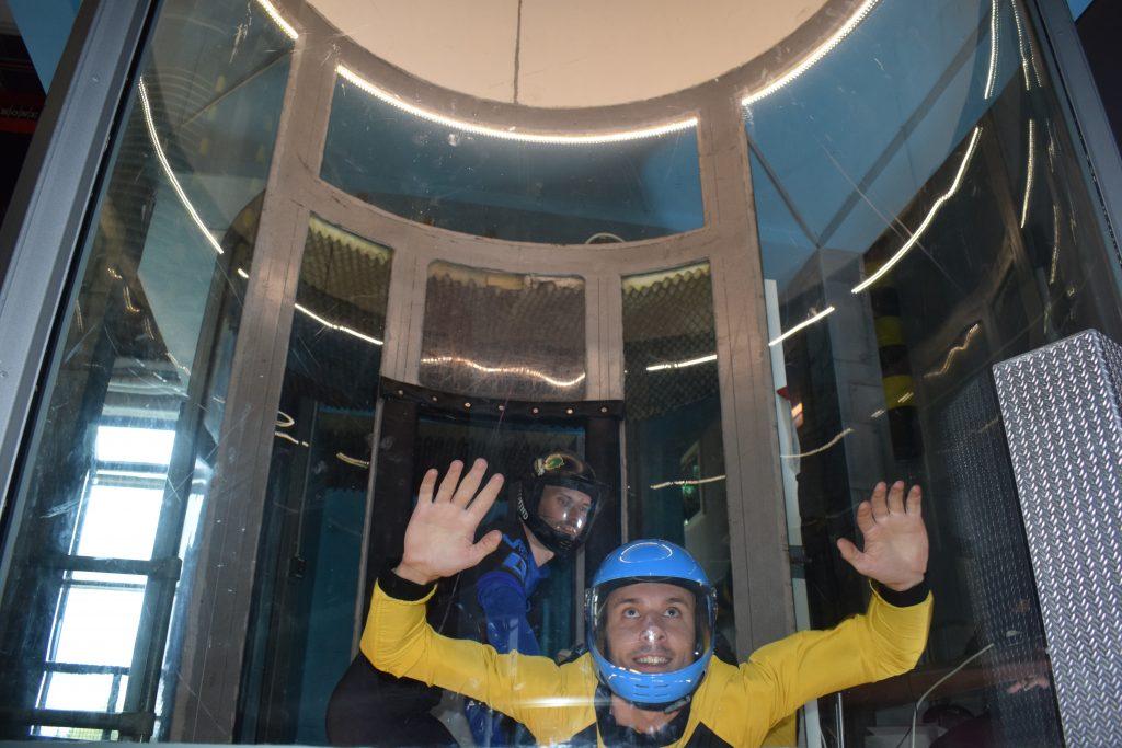 En ung gutt som flyr i vindtunnel med hjelp fra en instruktør. Indoor Skydive er en perfekt gave til den som har alt.