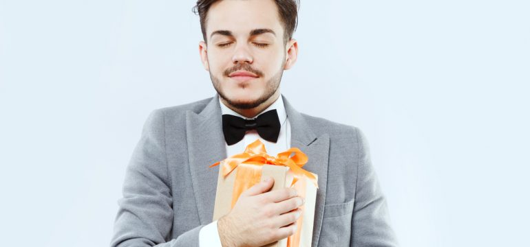 Nice brunette man posing with present on white background