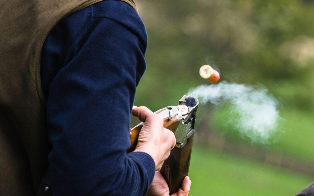 En mann som fyrer av et skudd på leirdueskyting. En gave til sønn som er glad i å skyte.