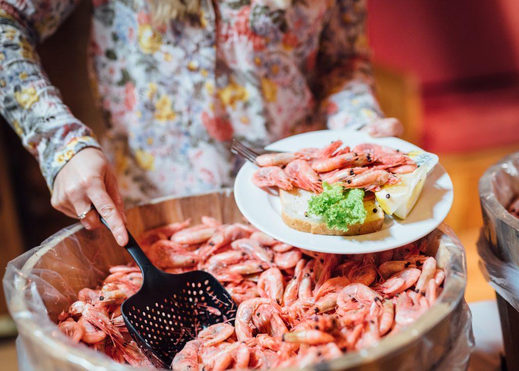 En dame som forsyner seg av en rekbuffet med ferske reker. Anbefalte aktiviteter i Oslo? Fjordcruise med rekebuffet er en sikker vinner.
