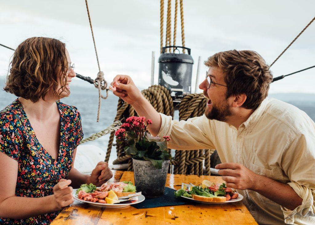 Par som nyter reker på dekk. Anbefalte aktiviteter i Oslo? Fjordcruise med rekebuffet er en sikker vinner.