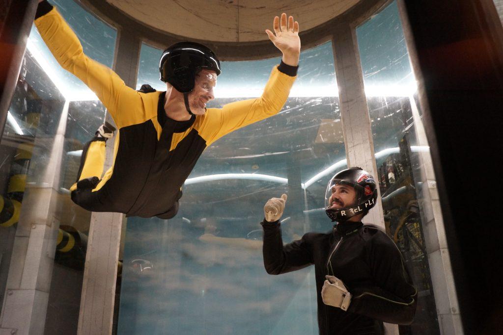 En mann som flyr i vindtunnel med veiledning fra en instruktør. Dette er en super gave til sønn.