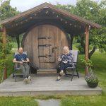Et par utenfor vintønn på en norsk vingård.
