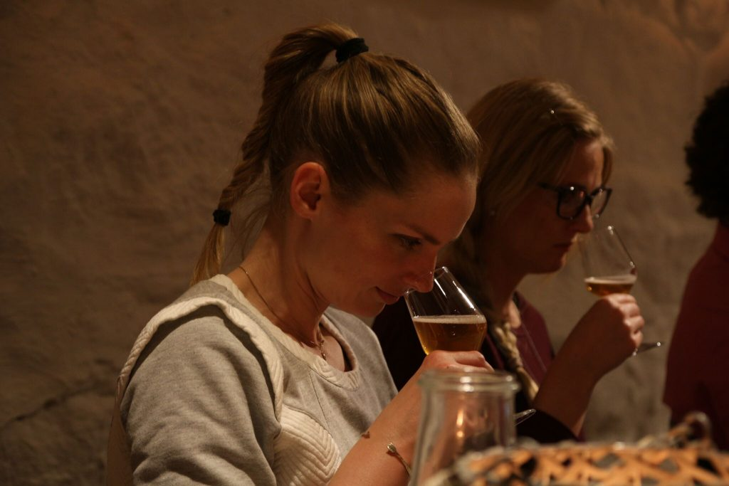 En ung dame som lukter på øl. Bli med på ølsmaking i Oslo.