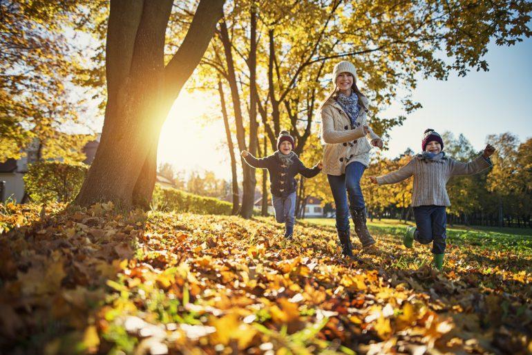 Mamma og to barn som løper gjennom høstløvet. Høstferie i Oslo 2017.
