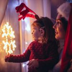 Jente som ser på julestjerne i vinduet sammen med moren sin. Julegavetips barn.