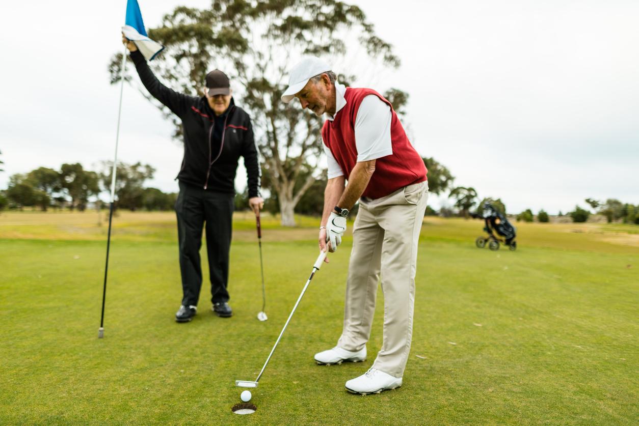 To eldre menn som spiller golf. Julegavetips pappa vil sette pris på.