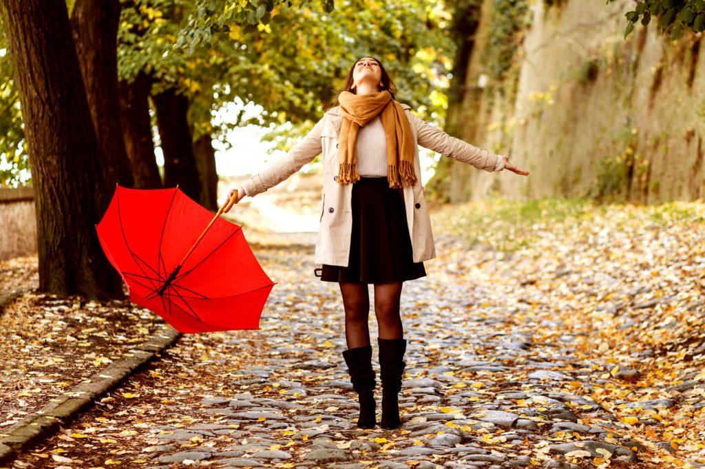 Ta med deg feriefølelsen inn i hverdagen. Glad jente i høstløvet med paraply.